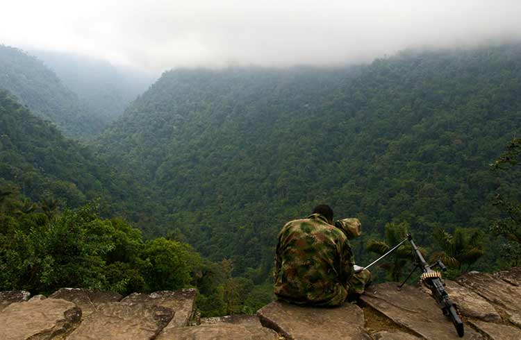 Man dressed in camouflage  sits on a ledge overlooking the mountains with a gun