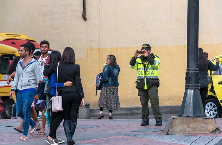 Police officer taking a picture of two women in Bogota