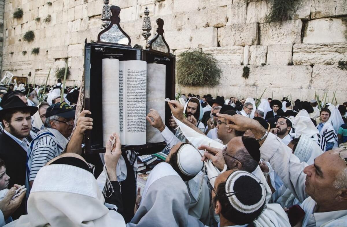 At the Wailing Wall, people celebrate the feast of Sukkot, a sacred celebration that lasts seven days. The Torah is uncovered and people approach to touch the sacred book.