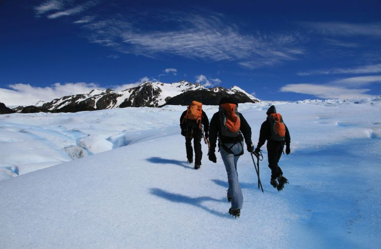 Three people hiking on a glacier in Chilean Patagonia