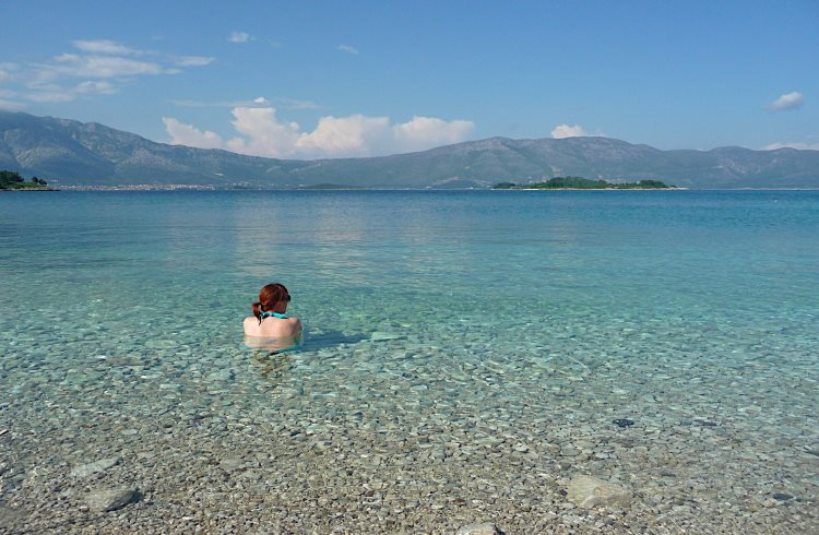 A woman enjoys the water at a beautiful, pebbly beach on the Croatian island of Korcula.