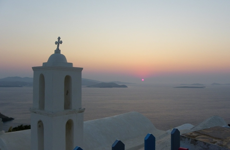 Sunrise over the white church tower on the Greek island of Astypalaia.