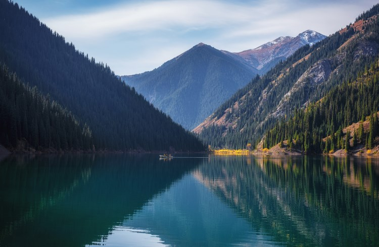 Forested mountains reflected in a blue lake at Kolsai Lakes National Park, Kazakhstan.