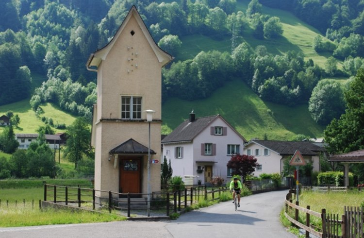 A cyclist pedals through the village of Linthal, Switzerland, on National Route No. 4.
