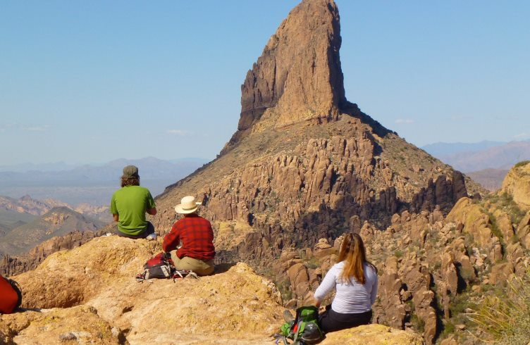 Hikers sit gazing at Weaver's Needle, an extinct volcanic plug in the Superstition Wilderness, Arizona.