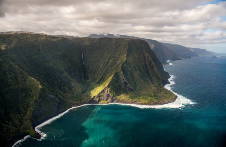 An aerial view of the steep green cliffs and turquoise waters of Molokai, Hawaii.