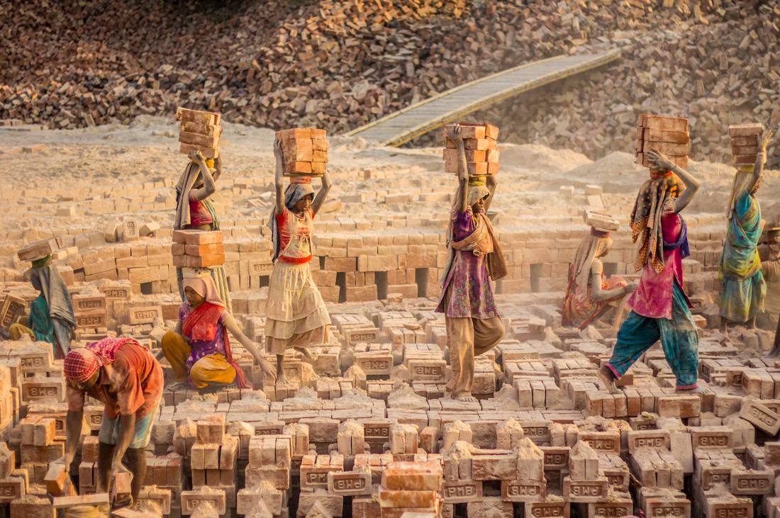 Group of girls carrying ready bricks out of the oven.