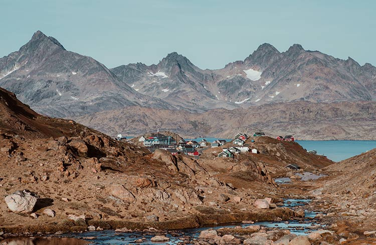 A colorful village sits between mountains in East Greenland