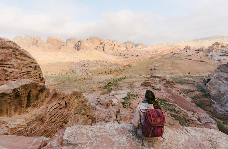 Woman sitting and looking at view of desert in Petra